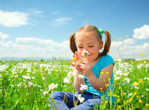 Little girl is smelling flowers on green meadow