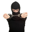 female thief in black balaclava with handcuffed hands