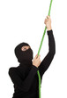 female thief in balaclava climbing on green rope