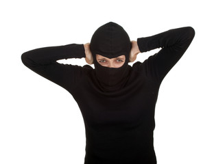 female thief in balaclava with hands on ears