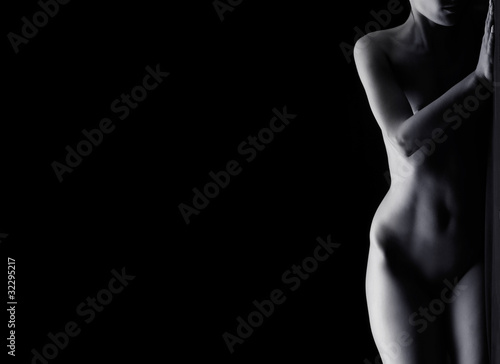 Beautiful naked body of a young woman on a black background