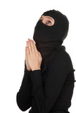 praying female thief in black clothes and balaclava