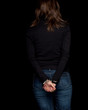 standing back woman with handcuffed hands, black background .