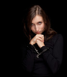 young woman with handcuffed hands, black background