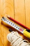 Tape measure, pencil, twine isolated on wooden background poster