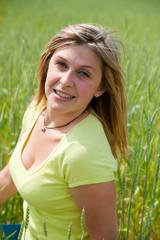 belle femme souriante dans un champs de blé vert