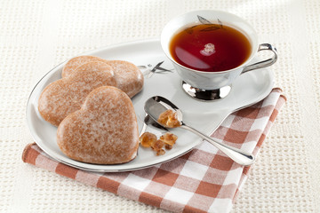 Cookies heart, brown sugar, spoon, black tea, saucer on tableclo