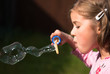 Beautiful little girl blowing a magical soap bubble