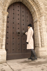 A woman in a white coat opens old gate