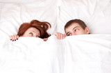 boy and girl are hiding under the blanket.