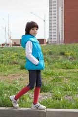 Скучающая девочка на фоне строительных кранов.