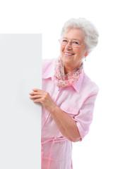 Seniorin hält Plakat