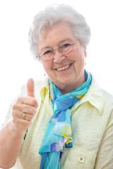 Lachende Seniorin zeigt Daumen