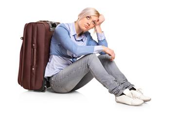 Sad tourist girl seated next to a suitcase