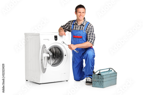 Repairman holding a spanner and posing next to a washing machine