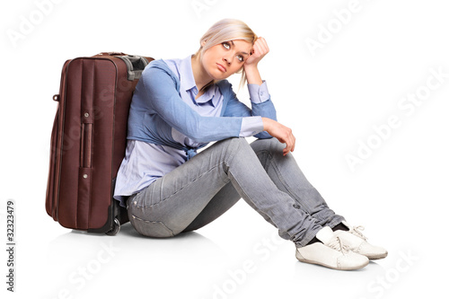 Sad tourist girl seated next to a suitcase
