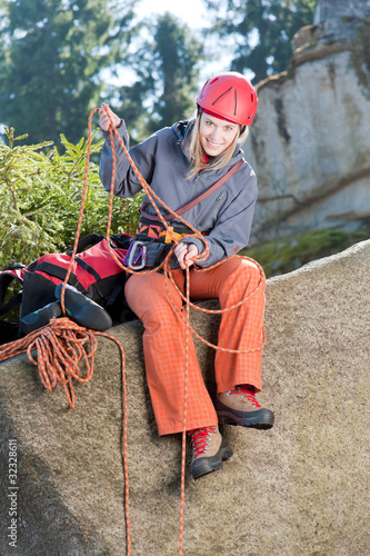 Active woman rock climbing holding rope