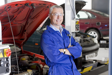 Smiling teacher leaning against car with automobile hood open in vocational school
