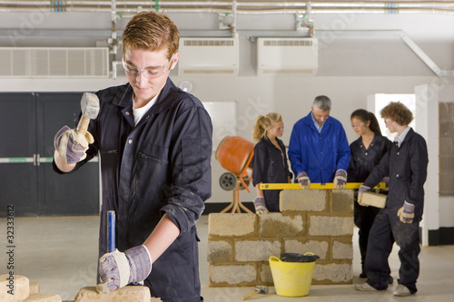 Student hammering chisel on brick in vocational school