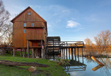 Historic wooden watermill with reflection