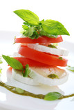 Fresh salad with goat cheese, tomato and basil pesto on a white