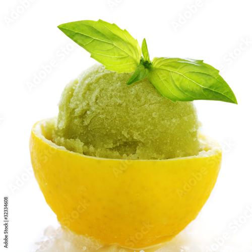 lemon- basil sorbet in cups of lemon on white isolated backgroun