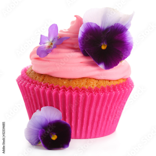 cupcake with cream and decorated with violets on white isolated
