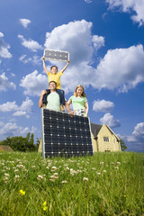 Happy family standing in green field holding solar panels