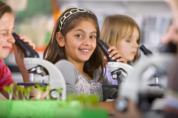 Smiling students peering into microscopes in science classroom