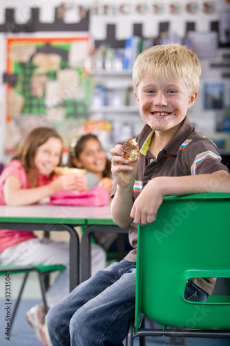 Smiling boy eating chocolate donut in school classroom