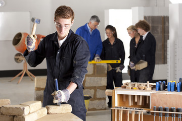 Student hammering chisel in bricklaying vocational school