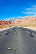 Asphalt Highway Disappearing into Desert Mountains