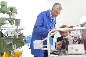 Teacher helping student constructing electric vehicle prototype in vocational school