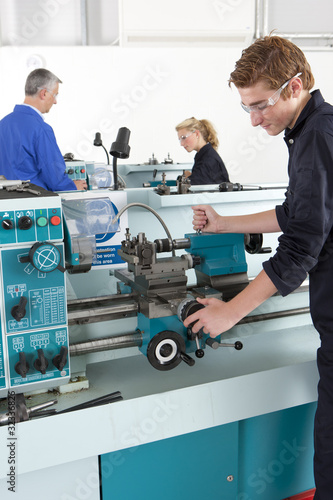 Teacher talking to students using lathe in vocational school