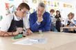Teacher watching student using soldering iron in vocational school