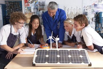 Teacher talking to students about wind power and solar panels in vocational school