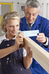 Teacher helping student measuring planed wood in vocational school