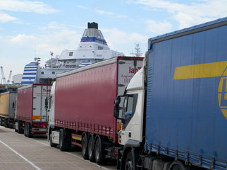 Semi-trucks in line waiting to board ferry boat