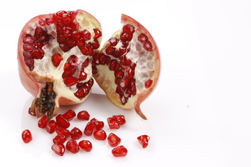fresh pomegranate with scattered seeds