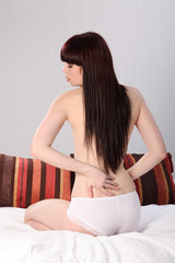 Back pain young semi naked woman examines herself