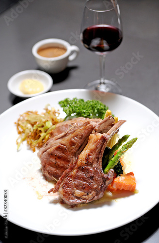 lamb chop meal with potato and carrot. Red wine with a glass in