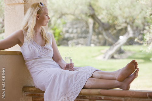 Tranquil woman sitting with feet up drinking water on porch