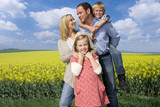 Happy family standing together near field of yellow blooming flowers