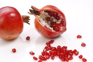 fresh pomegranates with scattered seeds