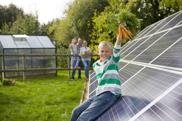 Boy holding bunch of carrots near large solar panels with family in background
