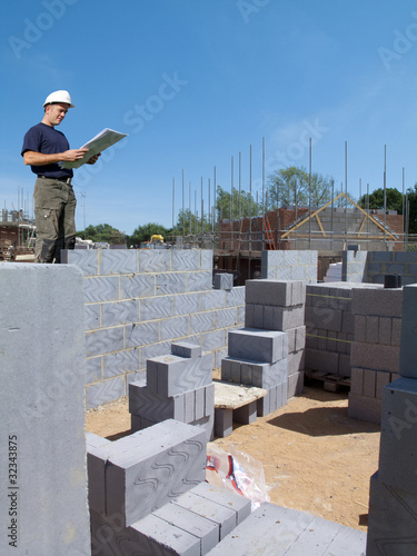 Construction worker holding blueprints on construction site
