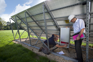 Technicians inspecting control panel on large solar panel