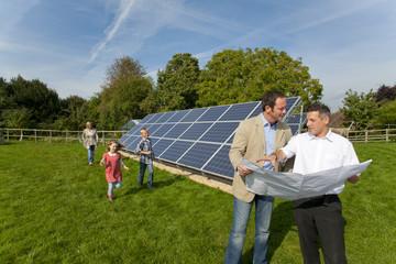 Technician holding blueprints talking to family near large solar panels