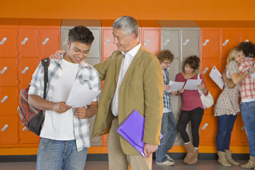 Student talking to teacher in school corridor about test results