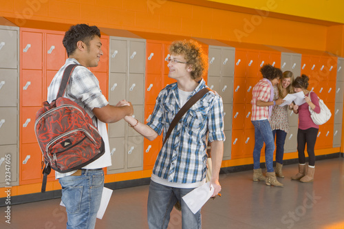 Excited students shaking hands after receiving good news about test results